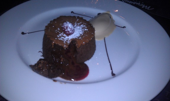 Le moelleux Warm chocolate and almond cake with rapsberry coulis in the center, hazelnut crust, hazelnut ice cream